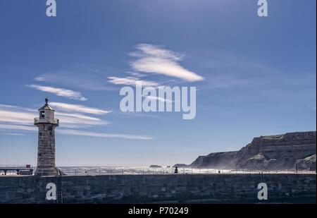 Early morning in Whitby with a lighthouse in the foreground. The light glistens on the sea and seaspray whips up by the cliff. - Stock Photo