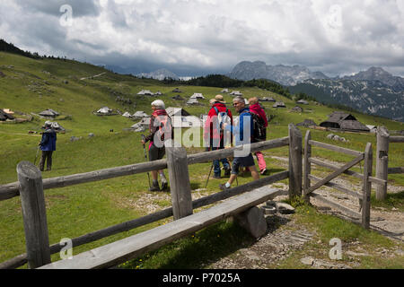 Walkers leave the chapel dedicated to Our Lady of the Snows, built in 1938 by the Slovenian architect Jože Plečnik, above the collection of Slovenian herders' mountain huts in Velika Planina, on 26th June 2018, in Velika Planina, near Kamnik, Slovenia. Velika Planina is a mountain plateau in the Kamnik–Savinja Alps - a 5.8 square kilometres area 1,500 metres (4,900 feet) above sea level. Otherwise known as The Big Pasture Plateau, Velika Planina is a winter skiing destination and hiking route in summer. The herders' huts became popular in the early 1930s as holiday cabins (known as bajtarstvo) - Stock Photo