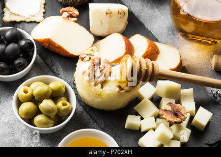 Snacks with wine - various types of cheeses, figs, nuts, honey, grapes on a gray background - Stock Photo