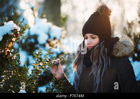 Young woman touch bush leaves outdoor winter portrait - Stock Photo