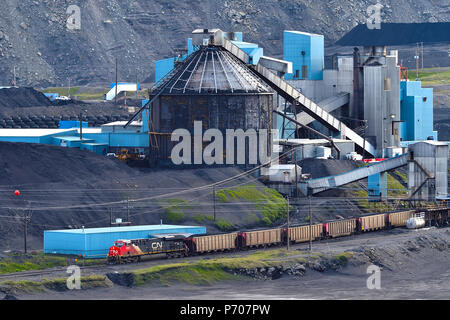 A horizontal image of a Canadian National Freight train loading raw coal from a processing plant in the foothills of the rocky mountains near Cadomin  - Stock Photo