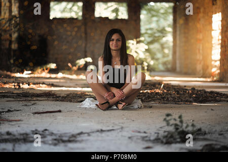 Young woman sitting in abandoned building Stock Photo