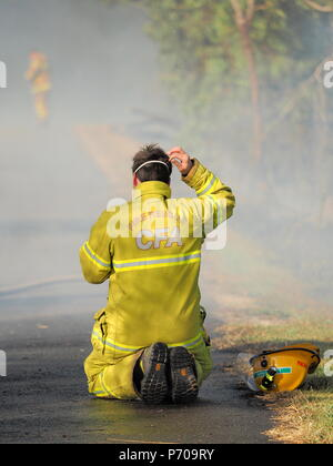 Melbourne, Australia - April 13, 2018: Exhausted Fire fighter at a bush fire in an suburban area of Knox City in Melbourne east. - Stock Photo