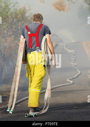 Melbourne, Australia - April 13, 2018: Fire fighter with rolls of fire hose at a bush fire in an suburban area of Knox City in Melbourne east. - Stock Photo
