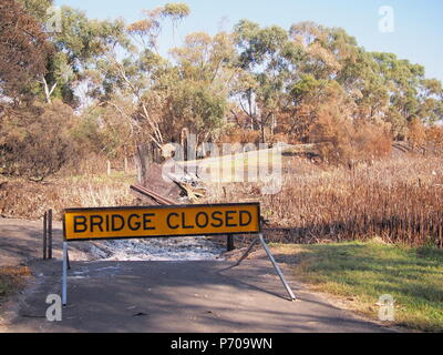 Remains of a burned down foot bridge and a warning sign after bush fire in an suburban area of Knox City in Melbourne east - Stock Photo
