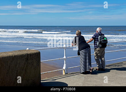 Couple on pier,gazing out to sea, Whitby, North Yorkshire, England UK - Stock Photo