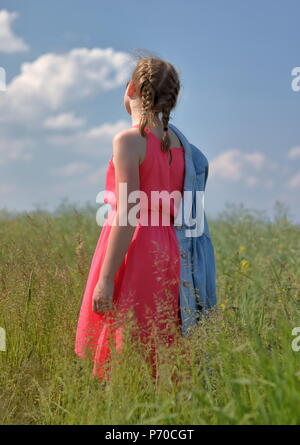 One white skin young blond hair girl stands back on meadow dressed in pink summer sleevless dress, sunny weather, blue sky whith nice white clouds - Stock Photo