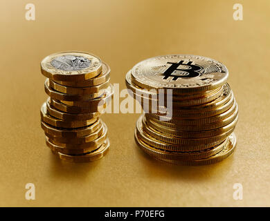 Golden Bitcoins stacked next to British pound coins - Stock Photo