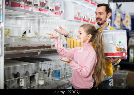 The man with the girl considering the range of different types of birds in a pet shop - Stock Photo