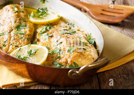 Delicious fish: baked trout fillets with garlic buttery herb sauce, lemon and parsley close-up in a copper frying pan. horizontal - Stock Photo