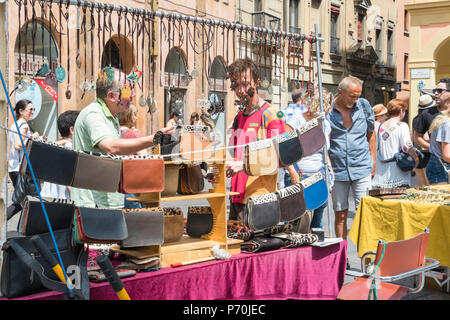 Market trader selling handmade leather handbags and necklaces in Bologna, Italy, Europe. - Stock Photo