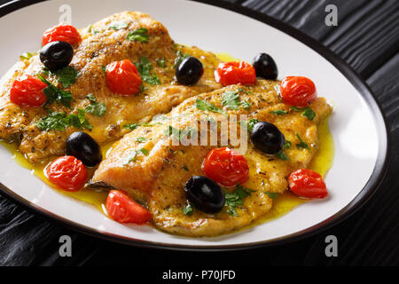 Italian food: fried trout fillets with garlic lemon butter sauce, tomatoes, parsley and olives close-up on a plate on a table. horizontal - Stock Photo