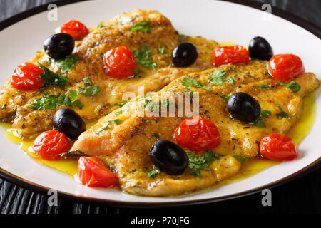 Delicious fried trout fillets with garlic lemon butter sauce, tomatoes and olives close-up on a plate on a table. Mediterranean food. horizontal - Stock Photo