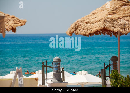 Summer Seaside Restaurant Terrace or Veranda Interior, Flattering Curtains, Metal Lanterns, White Wooden Furniture, Sea View. Leisure Concept, Lunch or Dinner Near The Sea and Chilling On The Beach - Stock Photo