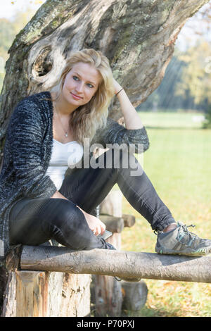 Portrait of cool young blond woman sitting in the sun rays in the autumn park. Vertically. - Stock Photo