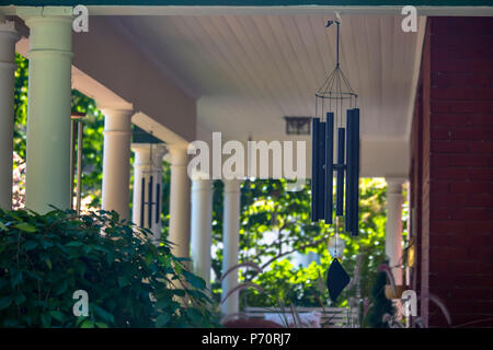 Wind chimes on a house with white pillars - Stock Photo