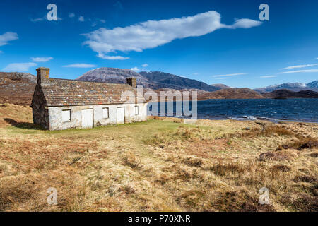 An abandoned cottage on the shores of Loch Stack in Scotland - Stock Photo