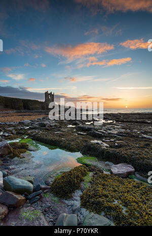 Beautiful sunrise at the ruins of Keiss Castle in Caithness on the far north east coast of Scotland near John O Groats - Stock Photo
