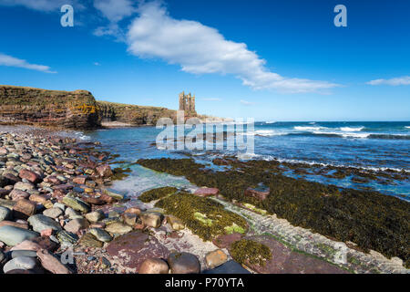 Blue skies over the ruins of Keiss Castle perched precariously on cliffs at Caithness on the north east coast of Scotland - Stock Photo