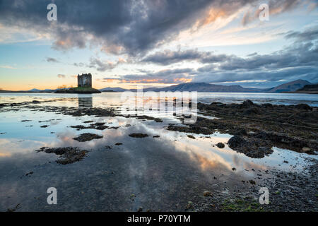 Sunset over Castle Stalker on the shores of Loch Linnhe near Appin in Scotland - Stock Photo