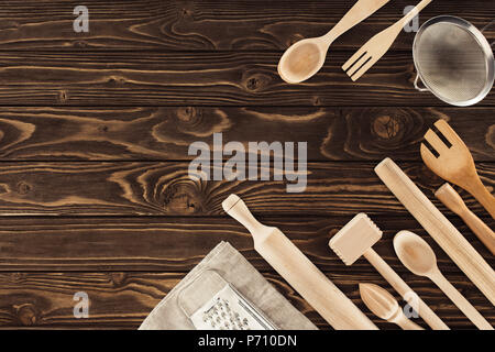 top view of arranged kitchen utensils, sackcloth and grater on wooden table - Stock Photo