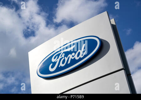 Ford dealership sign against blue sky. Ford is the second-largest U.S.-based automaker. - Stock Photo