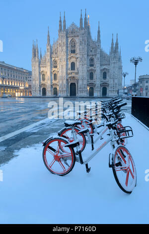 Parked bicycles covered by snow in Piazza Duomo, Milan, Lombardy, Northern Italy, Italy, Europe - Stock Photo