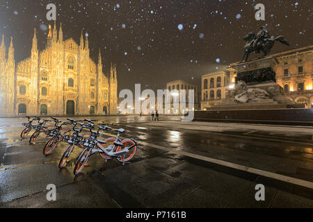 Parked bicycles in Piazza Duomo during a night snowfall, Milan, Lombardy, Northern Italy, Italy, Europe - Stock Photo