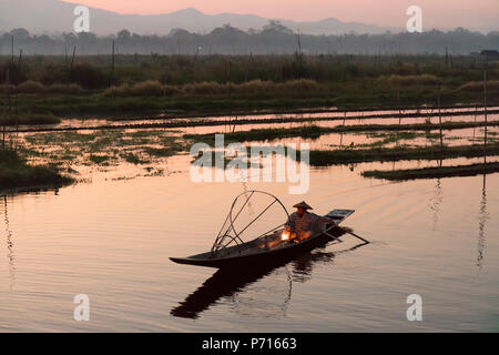 A fisherman keeps warm in his long tail fishing boat at dawn near the floating gardens on Inle Lake, Shan State, Myanmar (Burma), Asia - Stock Photo