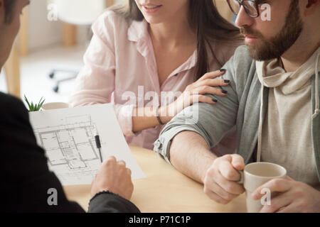 Millennial couple consulting about home design project in archit - Stock Photo
