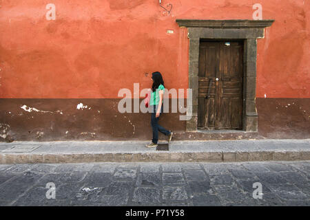 San Miguel de Allende, Guanajuato, Mexico - 2018: A woman walks in front of traditional colonial houses near the town's center. - Stock Photo