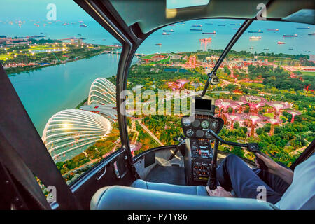 Helicopter cockpit interior flying on Singapore bay. Scenic flight above gardens by the bay skyline. Night urban aerial scene. - Stock Photo