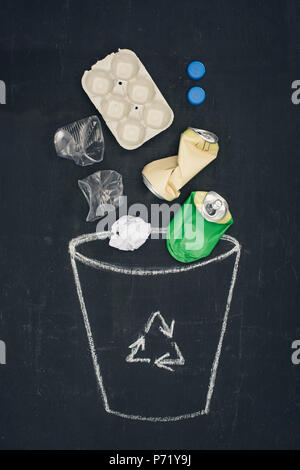 different types of trash falling into drawn trash bin with recycle sign on chalkboard - Stock Photo