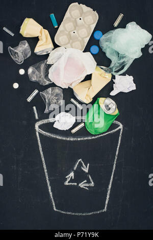 various types of trash falling into drawn trash bin with recycle sign on chalkboard - Stock Photo