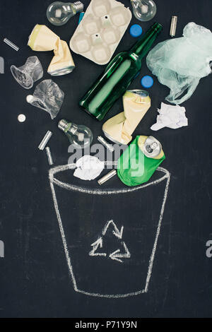 various types of trash falling into drawn trash can with recycle sign on chalkboard - Stock Photo