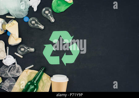 top view of various types of trash with recycle sign on black - Stock Photo