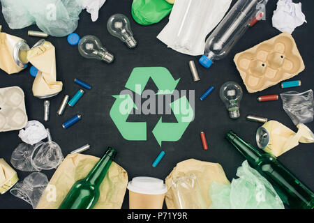 top view of various types of trash around recycle sign on black - Stock Photo