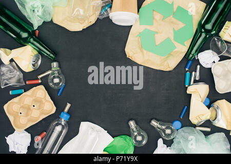 frame of various types of trash with recycle sign on black - Stock Photo