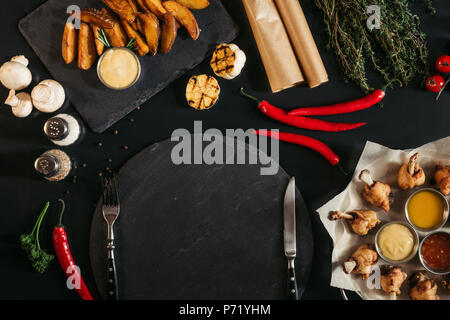top view of empty slate board with fork and knife, roasted potatoes and vegetables on black - Stock Photo