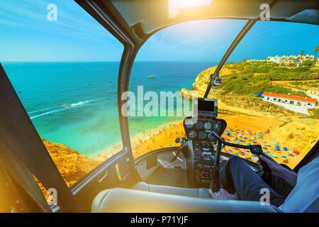 Helicopter cockpit interior flying on golden-colored cliffs of Praia de Benagil, Algarve near Lagoa, Portugal, Europe. Scenic flight above famous Benagil beach and Algar de Benagil. - Stock Photo