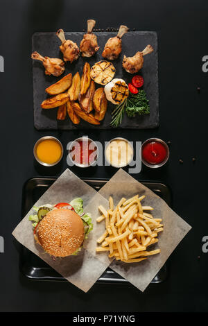 top view of french fries with delicious burger on tray, assorted sauces and slate board with roasted potatoes, grilled vegetables and chicken wings on black - Stock Photo