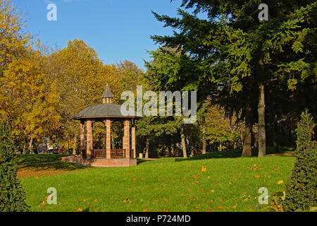 Gazebo in between autumn trees in `Bois de Boulogne` city park on a sunny day with blue sky in Paris, France - Stock Photo