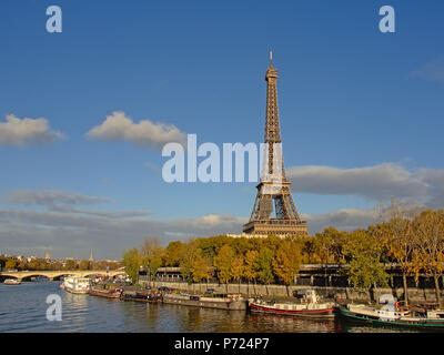 The famous Eiffel tower along river Seine with it`s house boats along a quay with autumn trees on a sunny day in Paris, capital of France - Stock Photo