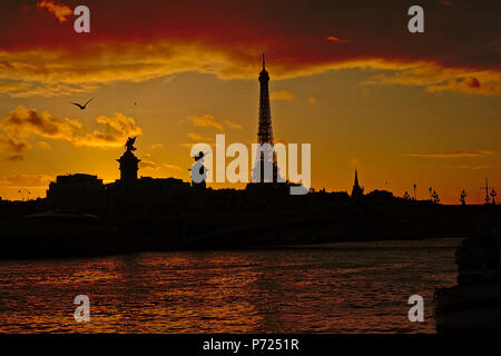 Silhouette of Eiffel Tower and Pont Alexandre III bridge along river Seine on a warm colourful evening sky with dark clouds - Stock Photo