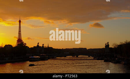 Silhouette of Eiffel Tower and Pont Alexandre III bridge in Paris on a warm orange evening sky with clouds - Stock Photo