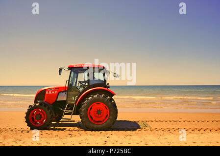 Red tractor on beach against blue sea and sky - Stock Photo