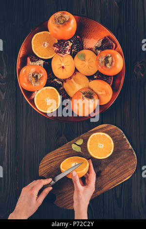 cropped image of woman cutting orange on wooden board - Stock Photo