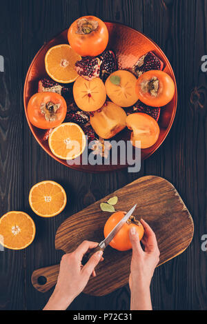cropped image of woman cutting persimmon on wooden board - Stock Photo