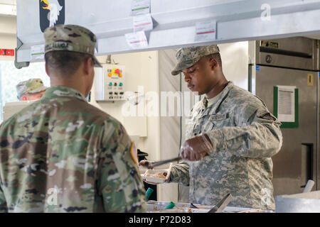 Spc. Ontroy Canty a food service specialist assigned to E Company, 6th Battalion, 101st General Support Aviation Battalion, 101st Combat Aviation Brigade, 101st Airborne Division, serves breakfast to Capt. Capt. Kris Sibbaluca in a containerized kitchen May 11, 2017 at Fort Campbell, Kentucky. Canty is part of the unit's Philip A. Connelly Program field feeding competition team, which won the division level in March and spent nearly two month preparing a site and training for the corps level competition. - Stock Photo