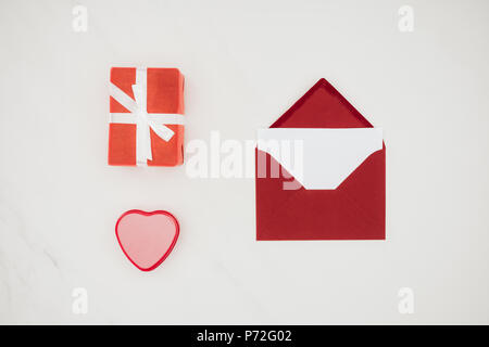 top view of red envelope with blank paper and gift boxes isolated on white - Stock Photo